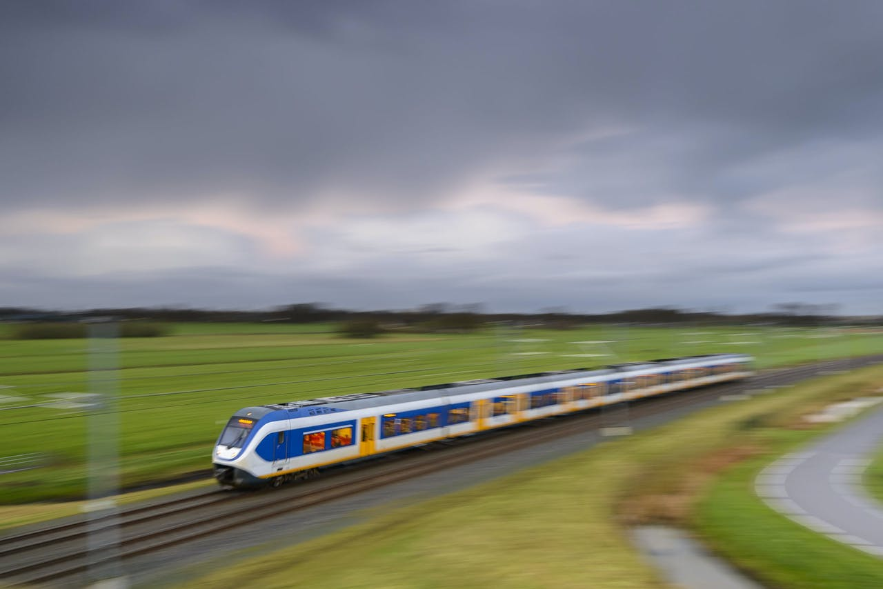 White and blue Dutch commuter passenger train driving through a rural landscape on a dark and rainy fall day. Image with speed effect from the motion blur.